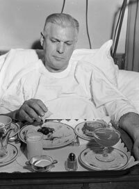 A cardiac patient looks somewhat skeptically at his tray of low-sodium food, circa 1955.