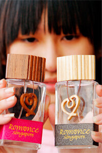 """A woman holds """"Romance Singapore Eau de Parfum"""" in 2004. The perfumes, aimed at getting Singaporeans in the mood, were used in a campaign to boost the republic's declining birth rate."""