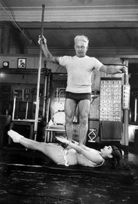 Joseph Pilates balances on the stomach of his student -- the opera singer Roberta Peters.