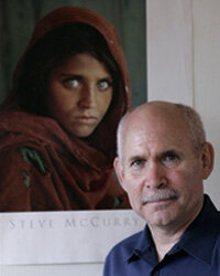 Photographer Steve McCurry poses with his famous portrait of an Afghan girl in Sept. 2008.