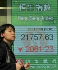 People walk past a stock board displaying the Hang Seng Index in Hong Kong, Jan. 22, 2008.