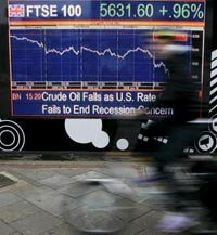 A cyclist passes a financial display screen showing the FTSE 100. See more recession pictures.