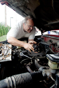 Henry Beghtol, a mechanic for over 40 years, works on his truck's engine in Burlington, Iowa.