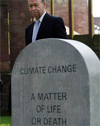 Climatologist and NASA scientist Dr. James Hansen stands next to a mock gravestone at a climate change campaign action day in England on March 19, 2009.