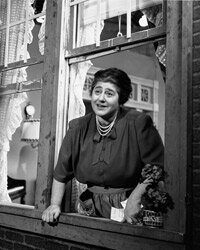 """Gertrude Berg smiles as she leans out of a window in a scene from """"The Goldbergs,"""" the first sitcom."""