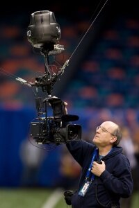 """一名乐动-软件技术人员在活动前检查一个Skycam。""""border="""