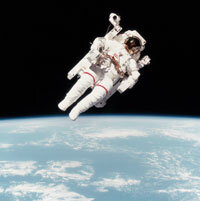 Astronaut Bruce McCandless II using a manned maneuvering unit (MMU) outside of the Space Shuttle Challenger. This was the first untethered spacewalk in history.