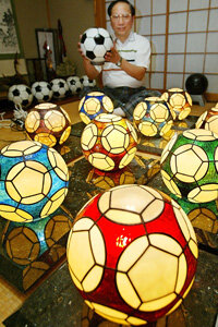 Stained glass isn't only used for religious windows. Here, Kazuhide Yoshikawa displays his original soccer ball-shaped lampshades built of stained glass at Hirakata in Osaka Prefecture, western Japan.