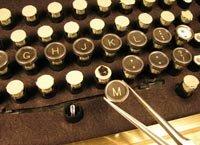 Jake von Slatt applies old typewriter key faces to the keycap in a modern computer keyboard.