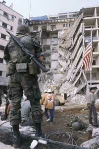 A U.S. Marine stands guard as rescue workers search the rubble of the U.S. embassy in Beirut for bodies following the 1983 suicide attack.
