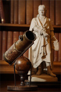 Telescopes have been around for ages, or rather, centuries. You're looking at one made by Isaac Newton. That's a statue of the great brain, too.