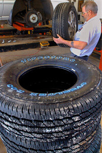 Tire specialist Vic Howlett installs tires on a vehicle at Lauterbach Tire and Auto Service in Springfield, Ill.
