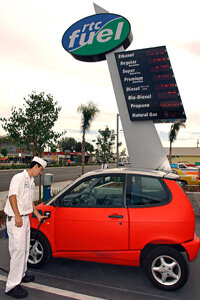 Regional Transportation Center attendant John Palma plugs a charger into a Think City electric car at the RTC in San Diego, Calif., on Aug. 11, 2003.
