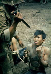 A Vietnamese paratrooper threatens a suspected Viet Cong soldier with a bayonet during an interrogation in 1962.