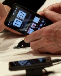 A visitor examines an HTC smartphone at the CeBIT Technology Fair in Hannover, Germany.