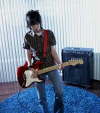 Why so glum, solo rocker? Get on the Net and form a virtual band! See more guitar pictures.