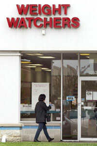 A client walks towards an entrance to a Weight Watchers meeting location May 18, 2004, in Arlington Heights, Illinois. With thousands of meetings around the country -- and the world -- dieters are able to find the support they need when they need it.