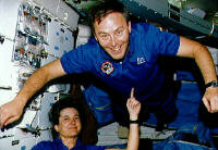 One astronaut lifts another with her finger. See more pictures of weightlessness.