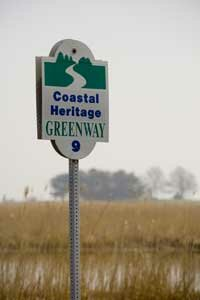 A sign identifies the wetlands route as a Coastal Heritage Greenway in Delaware.