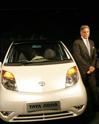 Ratan Tata poses in front of the Nano during its launch in New Delhi, India.