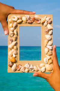 A homemade seashell frame, like the one pictured here, is the perfect mate for a beach vacation photo.