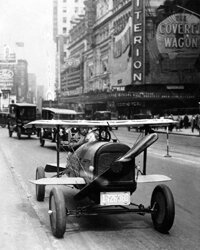A car with wings and a propeller protruding from the radiator grille drives through Times Square, New York. The invention of A.H. Russell of Nutley, New Jersey.