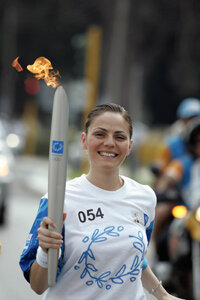 A torchbearer carries the flame during the 2004 Athens Olympic Torch Relay.