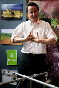 David Cameron cracks his knuckles after assembling a water delivery system with frontline Oxfam workers. See more bodily feat pictures.