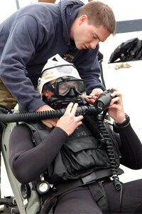 Lt. Evan Colbert gets helps with a MK-16 rebreather before a dive off Lima, Peru. Rebreathers have long been used by the military.
