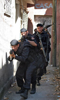 "Members of Brazil's Militarized Police patrol an alley in the squatter village of Cidade Alta (known as the ""City of God"") in Rio de Janeiro in 2007."