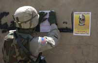 A soldier posts flyers over graffiti on a wall in Iraq as part of a Psychological Operations mission.