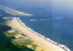 Changes in Assateague Island as a result of accelerated erosion from the man-made rock jetties of Ocean City Inlet (top: photo of the inlet, bottom: map of the area with outline showing the position of the island in 1849).
