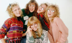 "A 1980s stock photo. The caption reads: ""Five friends smiling, wearing sweaters and eyeglasses."""