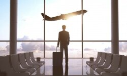 Man watches airplane take off from terminal