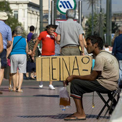 "A Greek beggar holds a sign reading ""I'm hungry."""