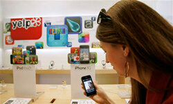 A woman looks at an iPhone inside an Apple store in Palo, Alto, Calif., on April 21, 2009, in front of a display promoting iPhone applications. See more iPhone pictures.