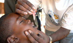 The district immunization officer administers the polio vaccine to a group of children in Gorakhpur, India during a National Immunization Day (NID) in 2000.