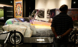 """A visitor to the Peterson Automobile Museum examines a lowrider 1953 Chevrolet ice cream truck named """"El Chavez Ravine"""" in Los Angeles, Calif."""
