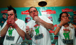 These three folks are competing in a corn beef eating contest on St. Patrick's Day in New York.