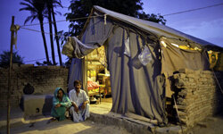 Allah Ditta and his wife Amna sit next to the temporary shelter at the site of their home in Muzaffargarh, Pakistan. The photo was taken in July 2011, a year after floods destroyed their house.