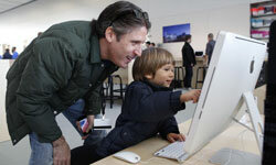An Apple employee and his son try out the Mac computers in the kids section of Chicago's Apple Store.