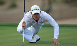 Golfer Camilo Villegas contorts himself into an interesting position to read the green.