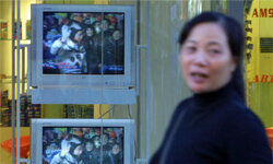 Business as usual in Beijing as a woman walks past a television announcing that China had successfully put a man in space.