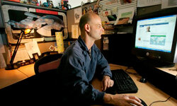 Curtis Soldano, associate producer at Electronic Arts, looks at his Facebook page at his cubicle in Redwood City, Calif., in 2008.