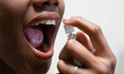 Woman using breath freshener