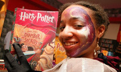 """A young fan brandishes her copy of """"Harry Potter and the Chamber of Secrets"""" at the Borders at Time Warner Center in New York City."""
