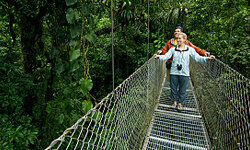 A couple takes a stroll on a rainforest canopy walkway in the Arenal Volcano area, Costa Rica.