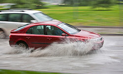 Vehicles pass through a flooded street during heavy rain in Santiago, Chile. See more car safety pictures.