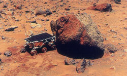 The Sojourner Rover uses its Alpha Proton X-Ray Spectrometer (APXS) to analyze the Yogi Rock on the surface of Mars during the Mars Pathfinder exploratory mission in July 1997.