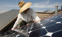 Employees of a solar company install panels on a residential rooftop in Santa Monica, Calif.